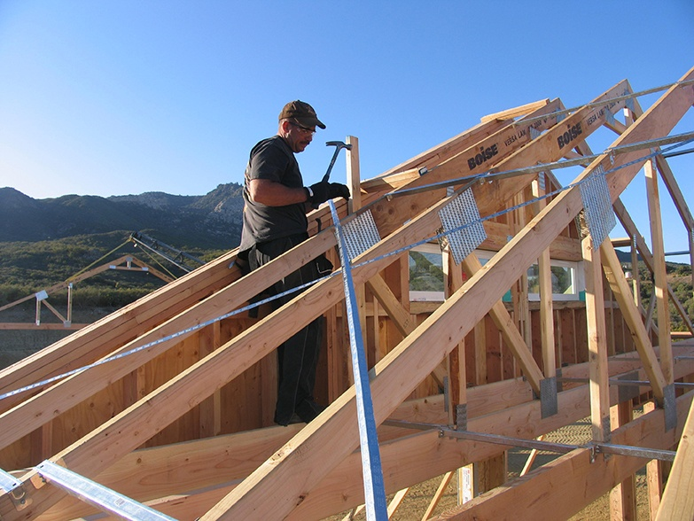 man hammering a house frame